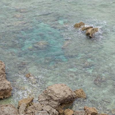 ゴツゴツした岩場と透き通る海の写真