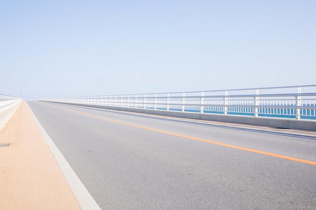 どこまでも続く伊良部大橋の道路の写真