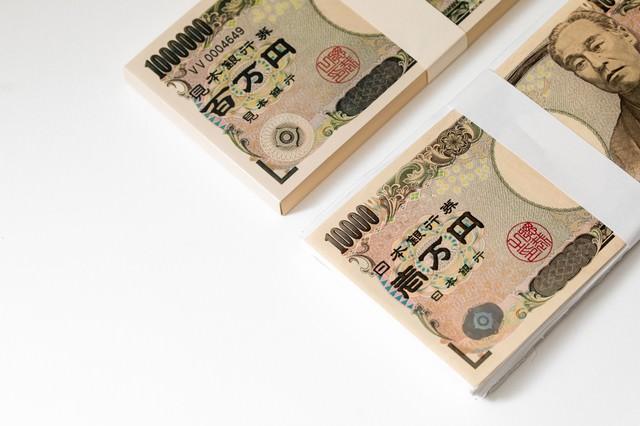 上が犯罪に使われた偽札の札束、下が真札が1枚だけの札束の写真