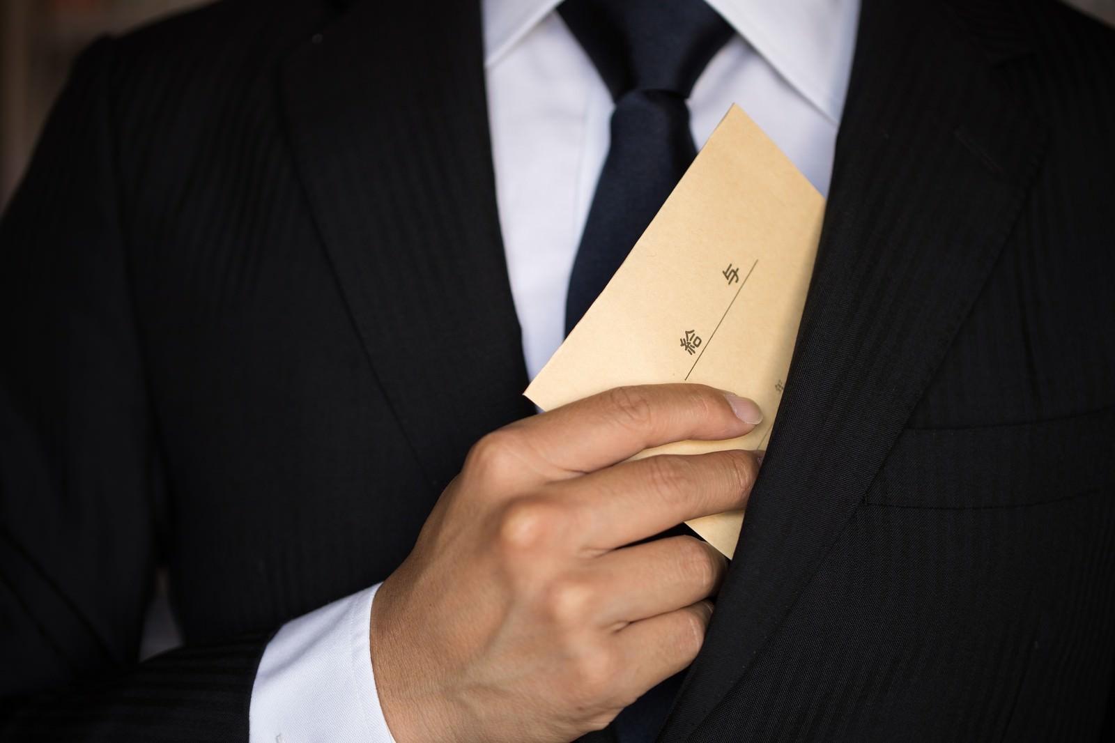 給与を内ポケットにしまうビジネスマン