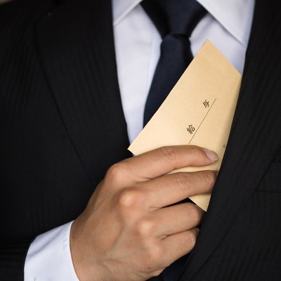 「給与を内ポケットにしまうビジネスマン」の写真素材