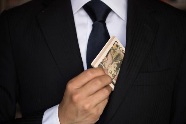 キャッシュ(偽札)をチラつかせるビジネスマンの写真