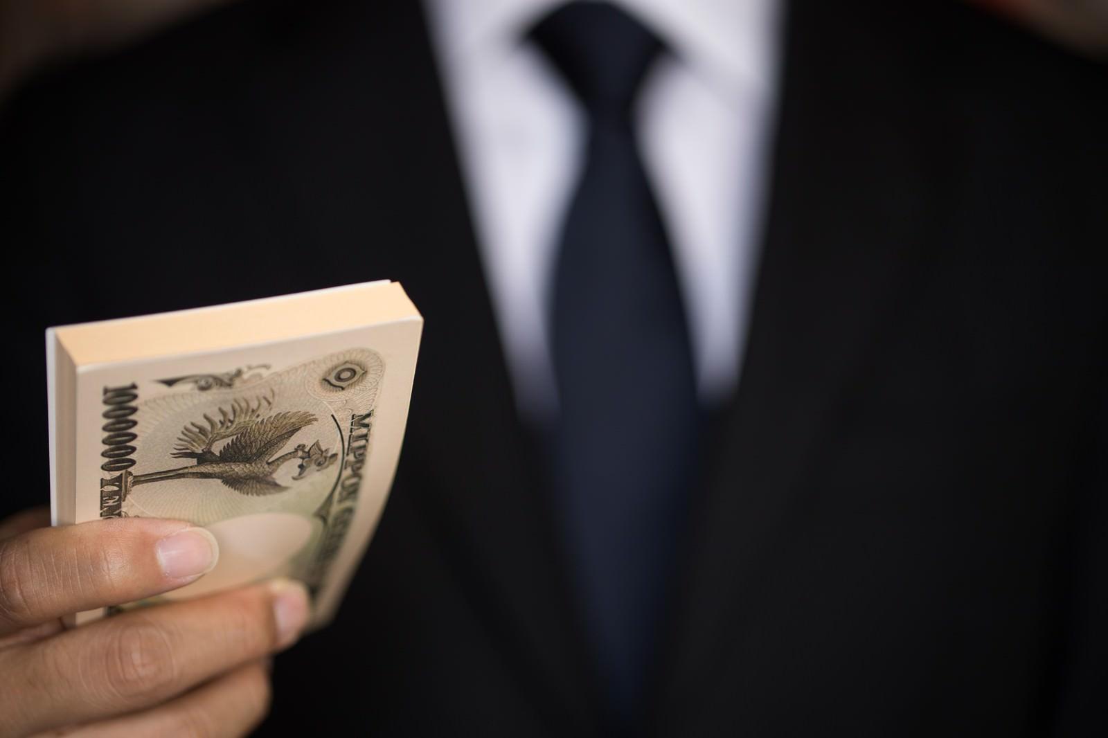 「「支払いはキャッシュで」と偽札を手渡す」の写真