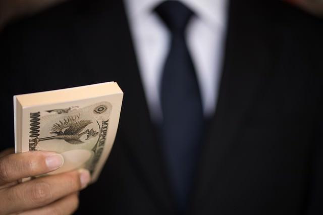 「支払いはキャッシュで」と偽札を手渡すの写真