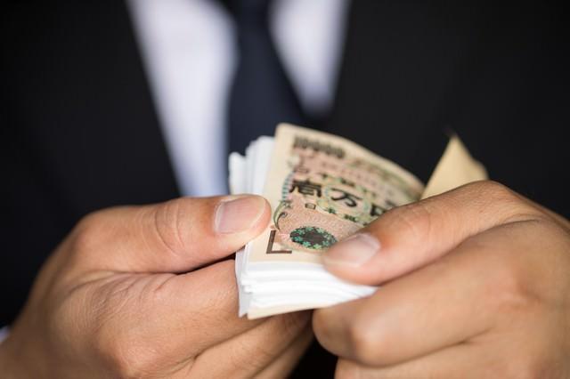 封筒から取り出した1万円札の束が明らかに偽装されていたの写真