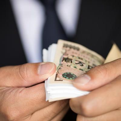 「封筒から取り出した1万円札の束が明らかに偽装されていた」の写真素材