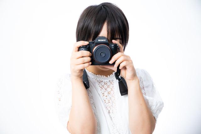 ファインダーを覗いてカメラを向ける女性の写真