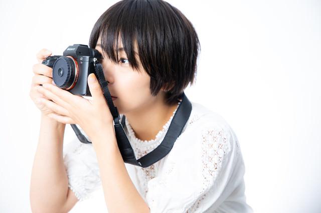 ファインダーを覗きながら構図を決める女子カメの写真