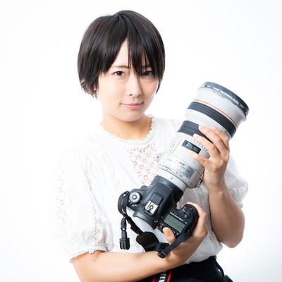 300mmの白レンズを抱える女性の写真