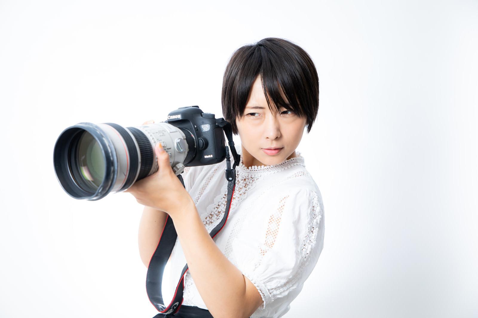 「望遠レンズを装着した一眼レフカメラを重たそうに持つカメラ女子」の写真[モデル:にゃるる]