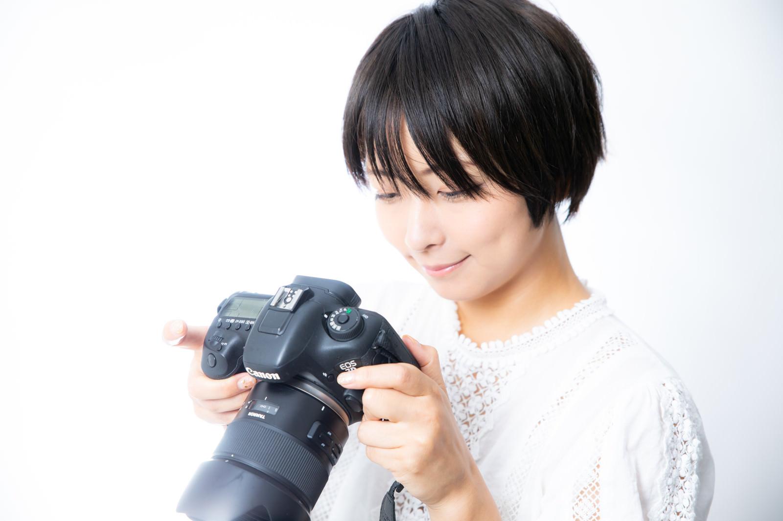 「撮影した写真を確認するカメラ女子」の写真[モデル:にゃるる]