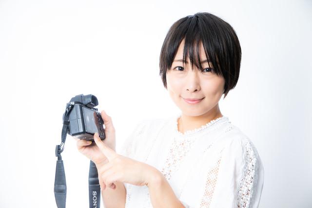 撮った写真を見てもらいたい嬉しそうなカメラ女子の写真