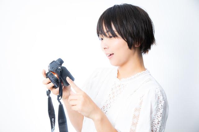 撮影した写真を嬉しそうに眺めるカメラ女子の写真