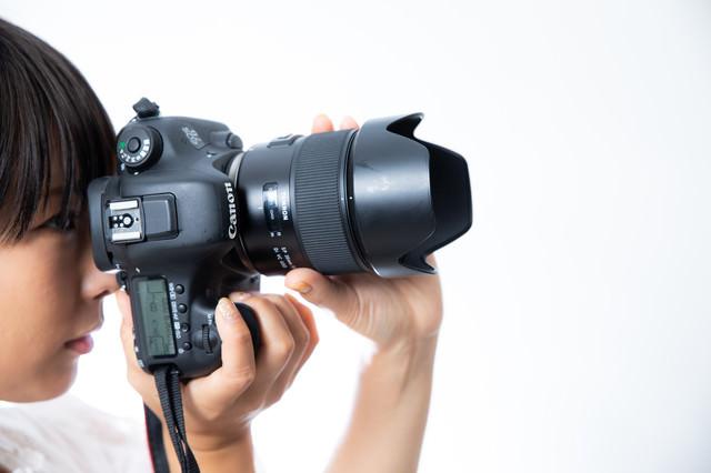 ファインダーを覗きながら縦構図で撮影するカメラ女子の写真