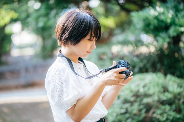 撮影した画像を確認してご満悦のカメラ女子の写真