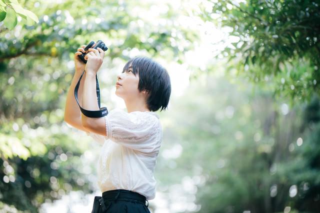新緑の中で撮影するカメラ女子の写真