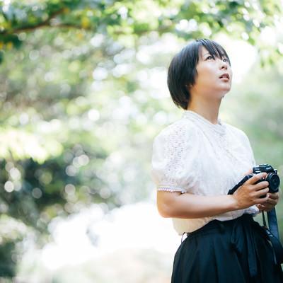 ミラーレスカメラを持った女性カメラマンの写真