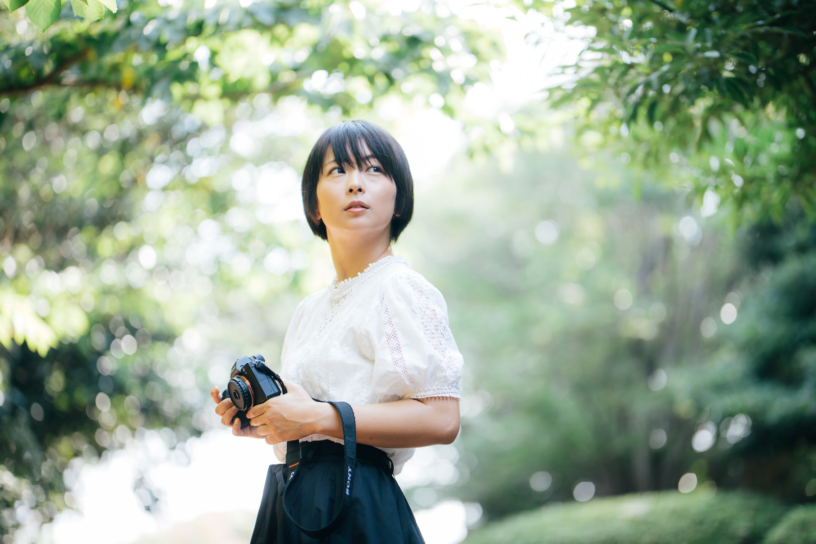「新緑の中、撮影場所を探すカメラ女子」の写真[モデル:にゃるる]