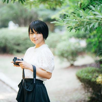 笑顔で会釈するカメラ女子の写真