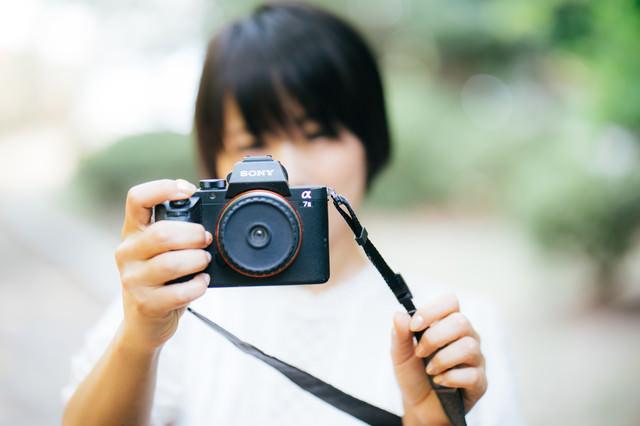 ミラーレスカメラを持って屋外撮影の写真