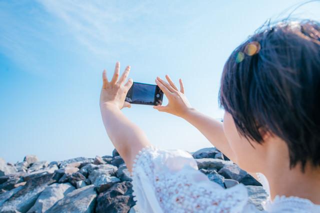 スマホで青空を撮影する女性の写真
