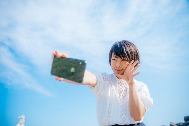 青空の下でスマホで自撮りする女子の写真