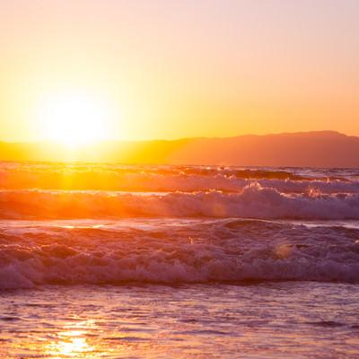 「荒波と日の出」の写真素材