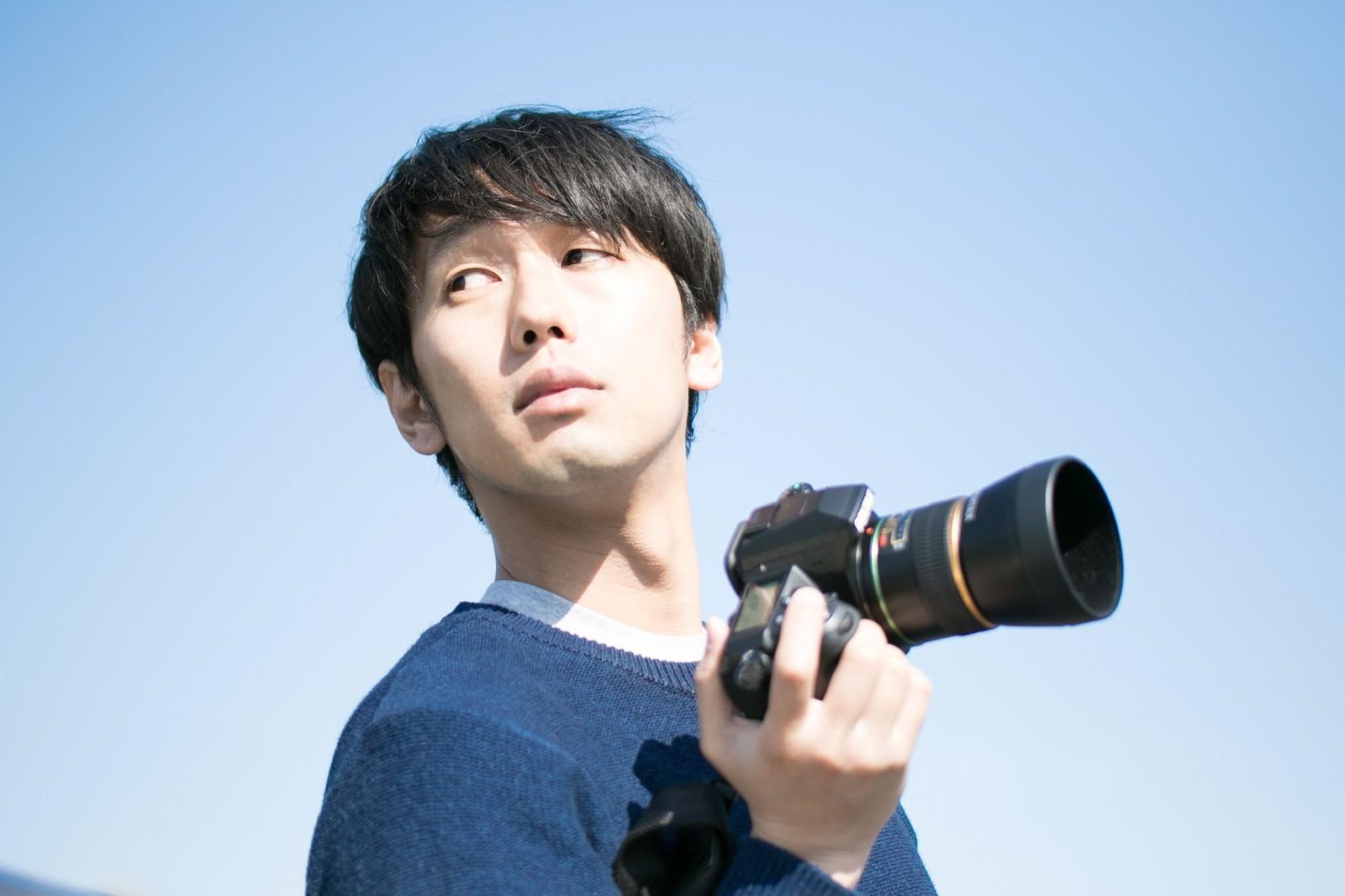 「ロケーションに納得がいかない不満気なカメラ男子」の写真[モデル:大川竜弥]