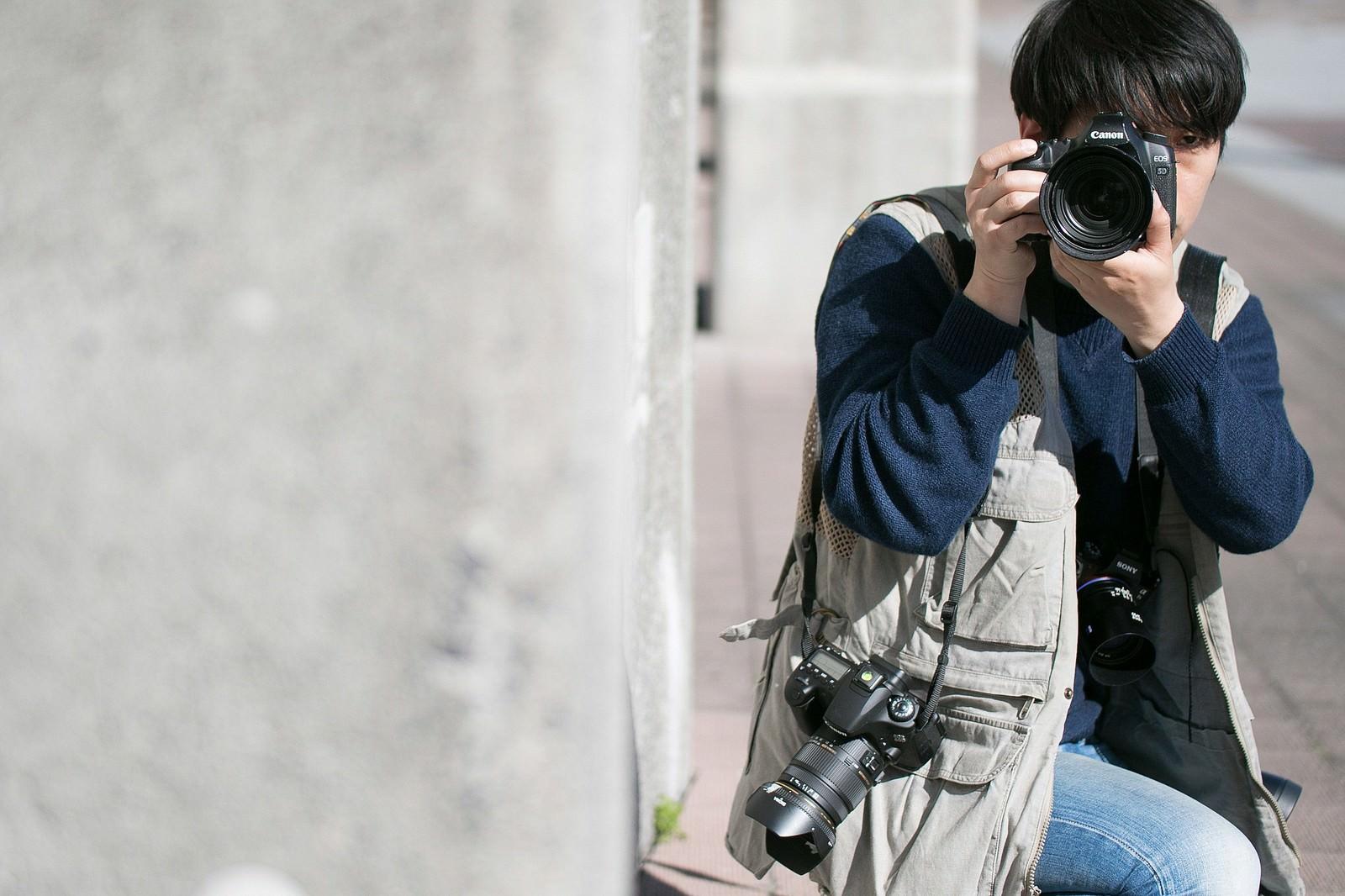 「物陰に隠れて撮影する戦場カメラマン」の写真[モデル:大川竜弥]