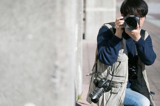 物陰に隠れて撮影する戦場カメラマンの写真