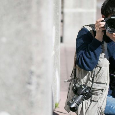「物陰に隠れて撮影する戦場カメラマン」の写真素材