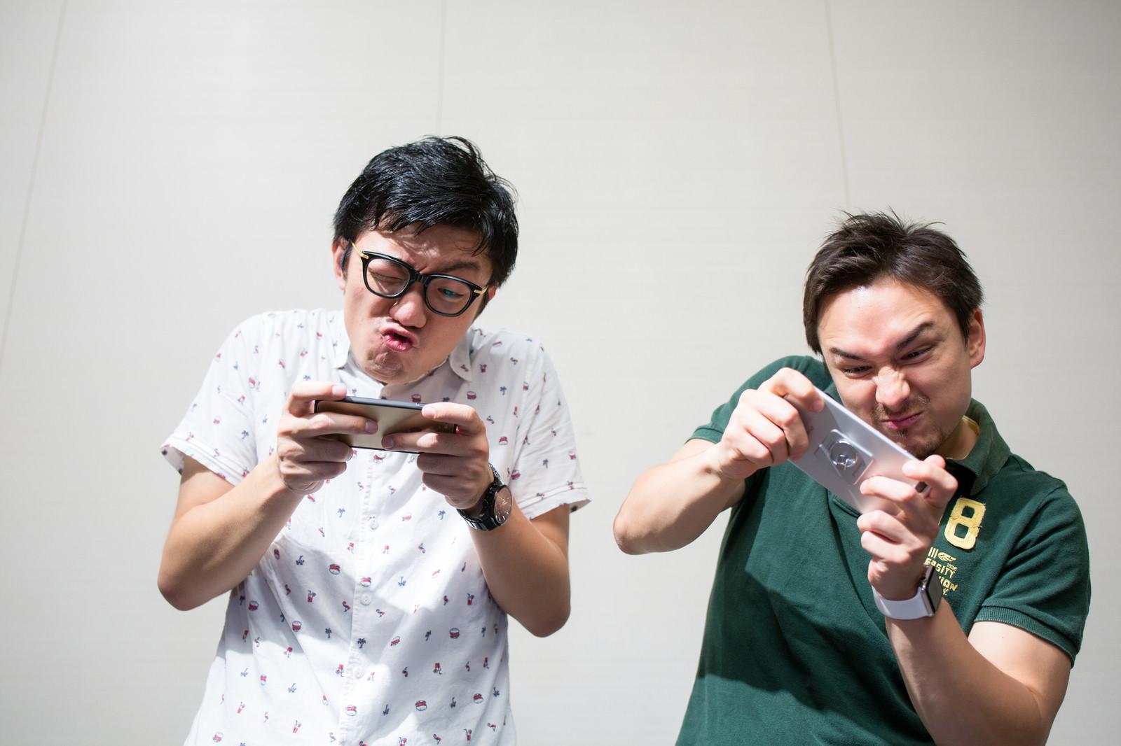 「スマホゲームに夢中なおっさん二人」の写真[モデル:Max_Ezaki ozpa]