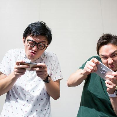「スマホゲームに夢中なおっさん二人」の写真素材