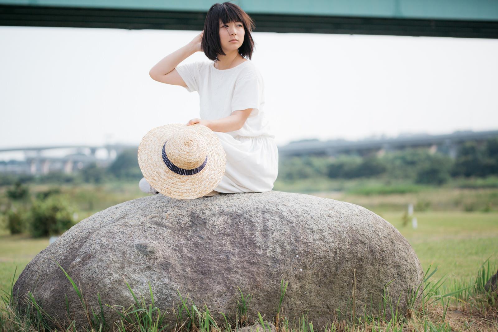 「石の上で辺を見回す麦わら女子」の写真[モデル:にゃるる]
