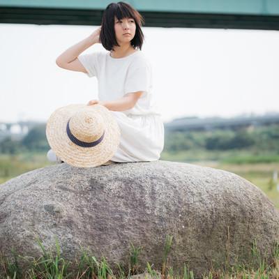 「石の上で辺を見回す麦わら女子」の写真素材