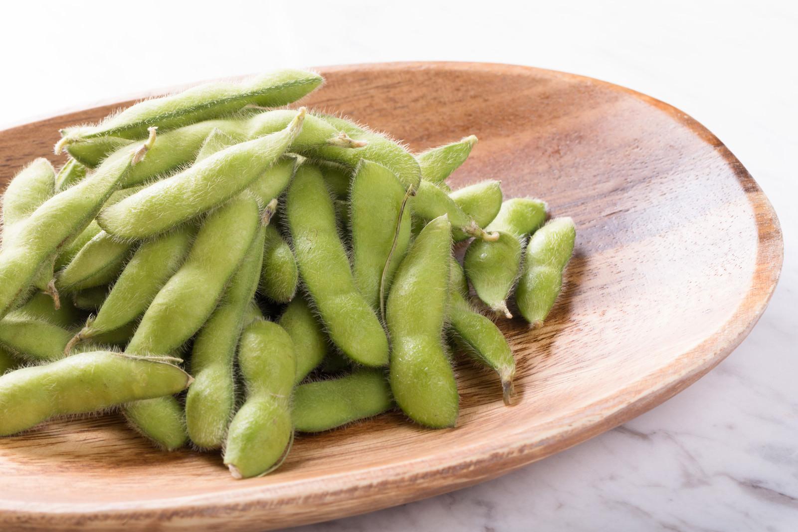 「木のお皿に乗った枝豆」の写真