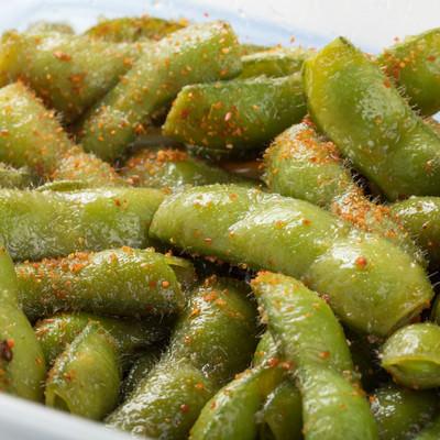 「ボイルした枝豆に、にんにくや七味唐辛子を混ぜて味をつける」の写真素材