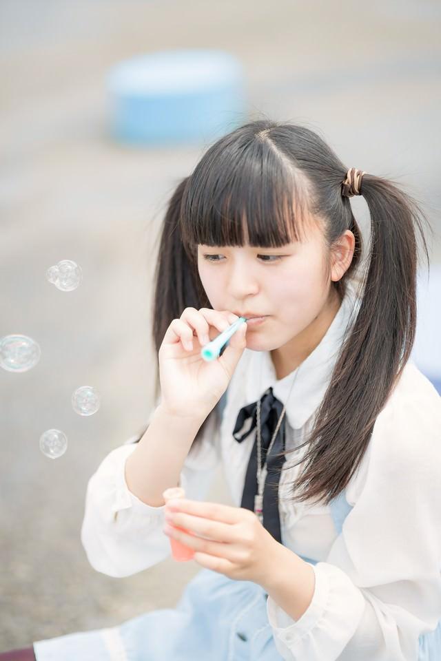 シャボン玉を吹くツインテールの女の子の写真
