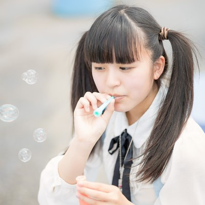 「シャボン玉を吹くツインテールの女の子」の写真素材