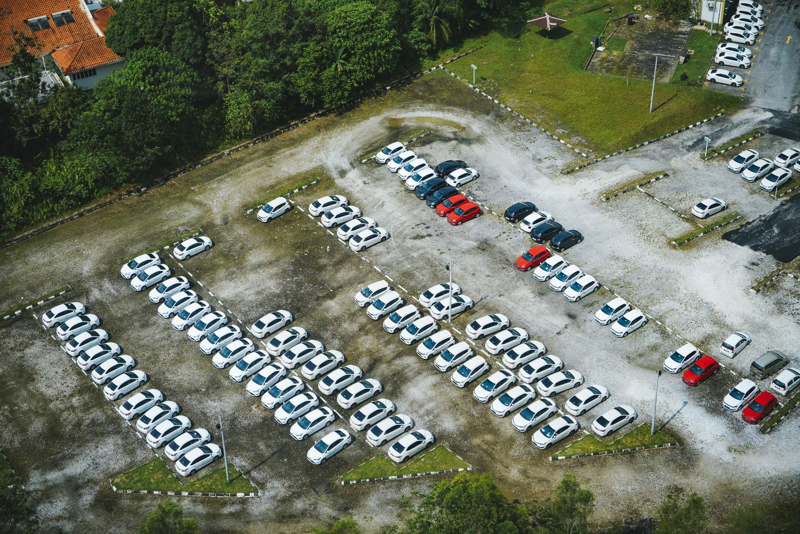 「広い駐車場に止まる白い車広い駐車場に止まる白い車」のフリー写真素材を拡大