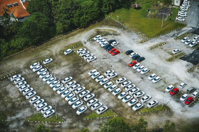 広い駐車場に止まる白い車の写真
