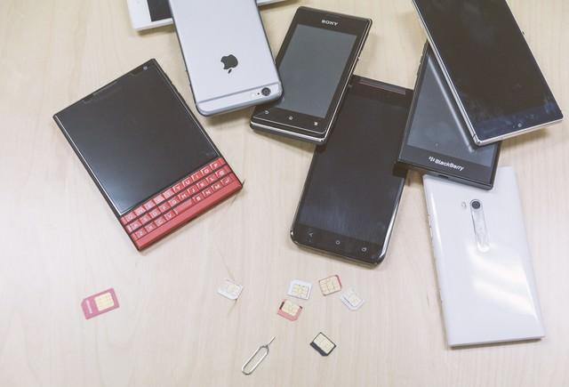 複数台の検証機(スマホ)と散らばるSIMカードの写真