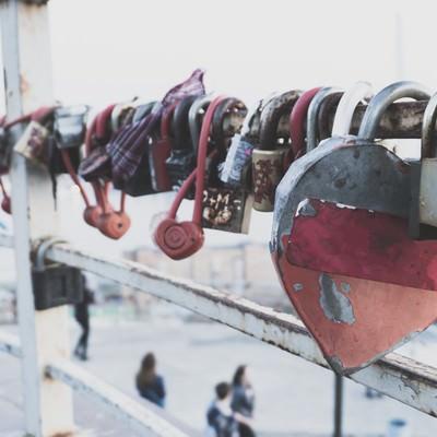 「手すりに取り付けられたハート型の南京錠」の写真素材