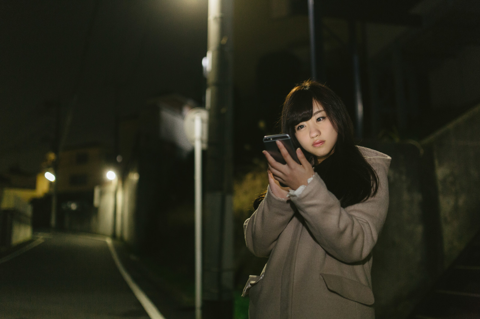 「夜道、スマホに夢中な女性夜道、スマホに夢中な女性」[モデル:河村友歌]のフリー写真素材