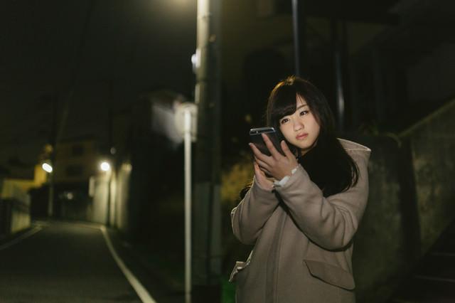 夜道、スマホに夢中な女性の写真