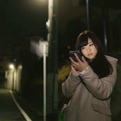 「夜道、スマホに夢中な女性」の写真素材
