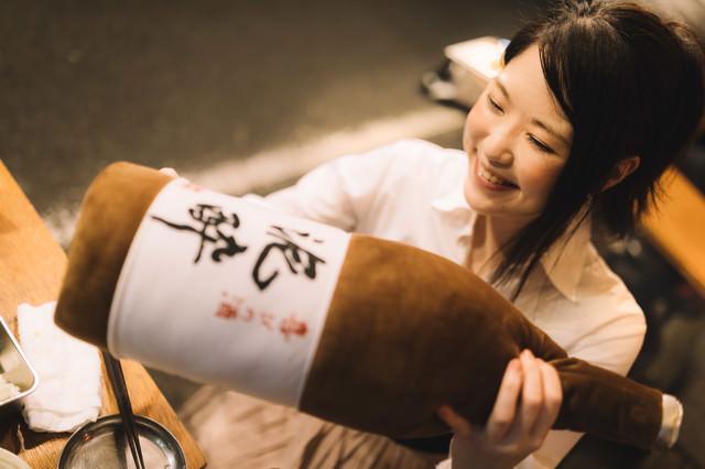「泥酔」と書かれた一升瓶の抱き枕をプレゼントされる女性の写真