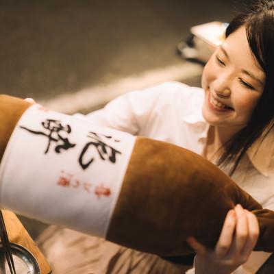 「「泥酔」と書かれた一升瓶の抱き枕をプレゼントされる女性」の写真素材