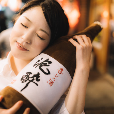 「何よりも一升瓶のお酒が大好きな女性」の写真素材