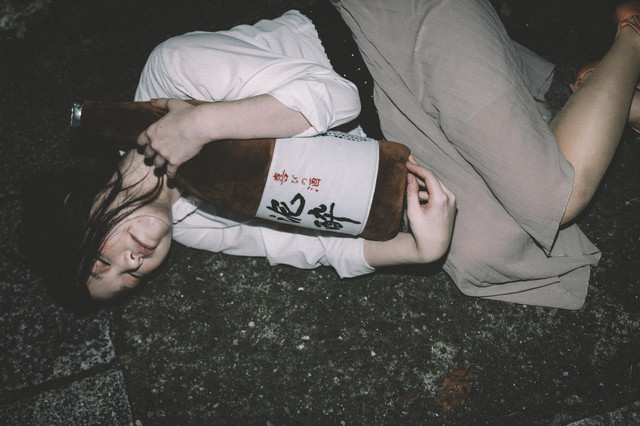 「[忘年会シーズン]泥酔して一升瓶を抱きながら路上で寝てしまった女性」のフリー写真素材